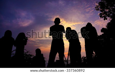 silhouette of a group of photographer who shoots a sunset in the mountains