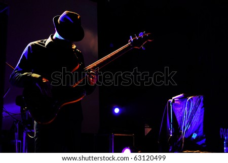 Silhouette of a guitarist enjoying the music - stock photo