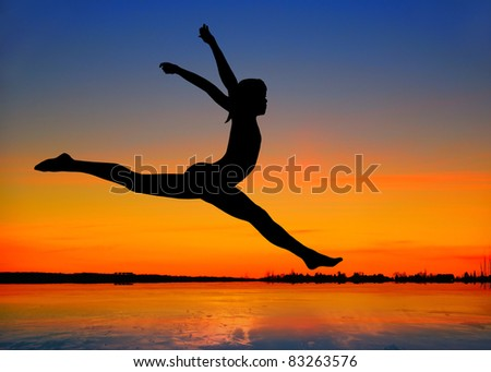 Silhouette of a gymnast girl jumping on the beach at sunset.