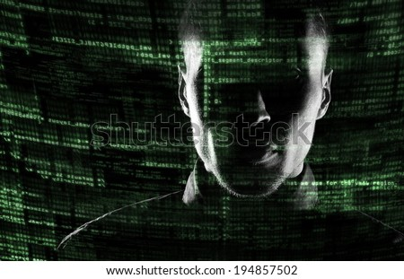 Silhouette of a hacker looking in camera with binary codes from monitor - stock photo