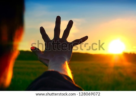 Silhouette of a Hand against a Sunset in the Summer Field - stock photo