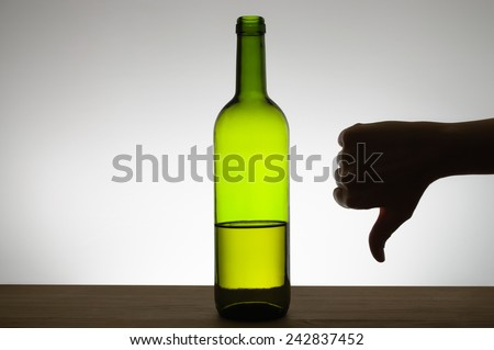 Silhouette of a hand showing thumbs down gesture next to a bottle of wine - stock photo