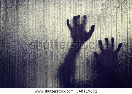 Silhouette of a hand the expression to be imprisoned, blur - stock photo