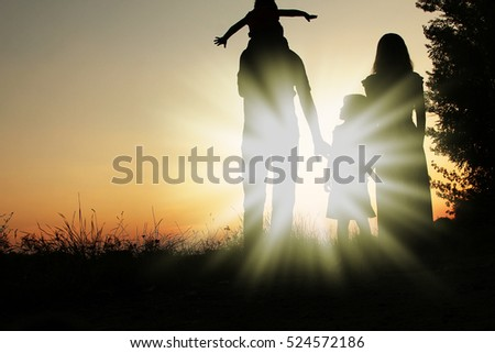 silhouette of a happy family on the nature of the sunset in the park