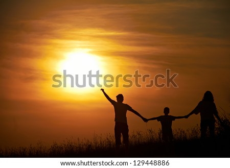 Silhouette of a happy family  with sunset background.