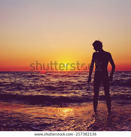 silhouette of a happy man admires the sunset on the sea. healthy lifestyle. freedom and inspiration. colorized and toned photo