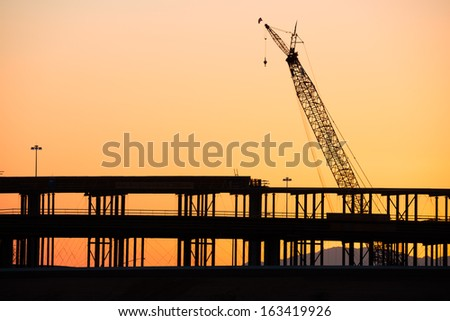 Silhouette of a highway overpass construction, with crane. - stock photo