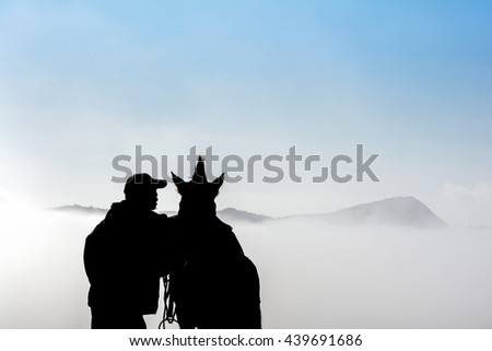 Silhouette of a horsemen resting on the sand dune with foggy / misty morning background at Bromo-Tengger-Semeru National Park, East Java, Indonesia