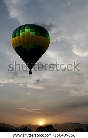 Silhouette of a hot air balloon floating in the sky against a surreal sunset.  - stock photo