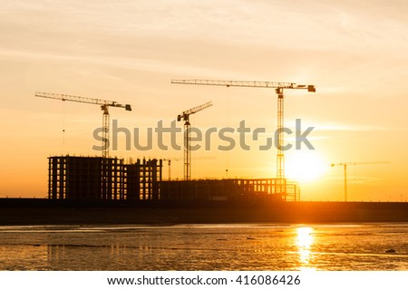 silhouette of a house under construction and the construction cranes in the background of orange sunset - stock photo