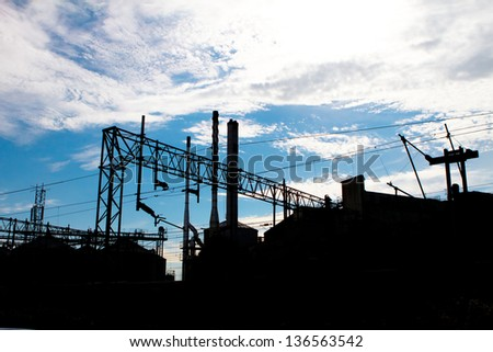 silhouette of a industrial factory against a blue sky - stock photo