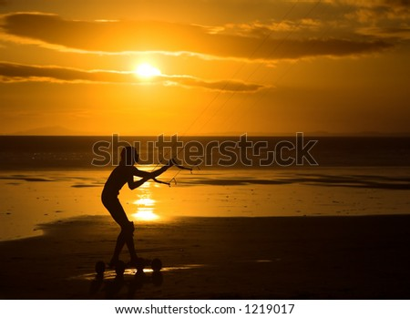 Silhouette of a kiter against a smashing beach sunset