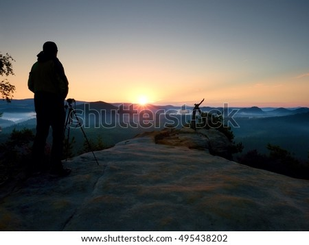 Silhouette of a landscape photographer on peak above misty valley. Colorful sun raising above misty landscape.