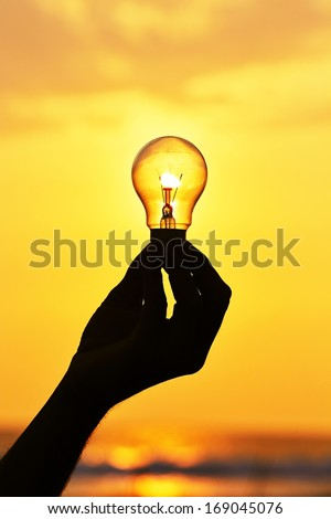 Silhouette of a light bulb at sunset. - stock photo