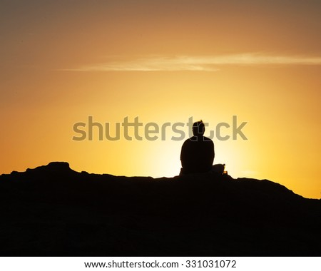 Silhouette of a lone man sitting in front of the sunset at the California shoreline. - stock photo