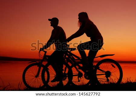 silhouette of a loving couple at the yellow or orange sunset sky background Copy space for inscription - stock photo