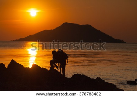 Silhouette of a male photographer standing on the rock at the beach of Ao Kra Ting Bay and preparing his equipment for sunset shot behind the island in the sea. (Koh Nom Sao)