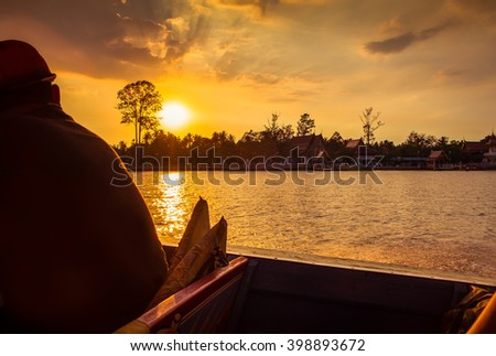 Silhouette of a male sitting on a boat in the water at Thailand. - stock photo