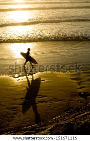 silhouette of a male surfer at sunrise on the gold coast - stock photo