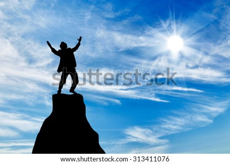 Silhouette of a man at the peak of the mountain on the background of the sunny sky