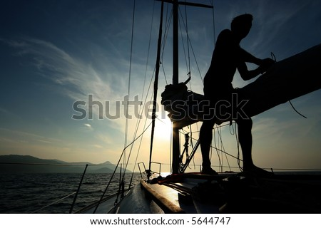 silhouette of a man at the sailing boat - stock photo
