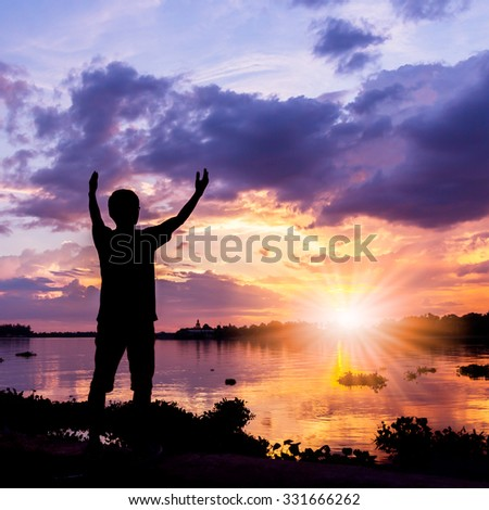 Silhouette of a man beside the river at sunset with sunray - stock photo