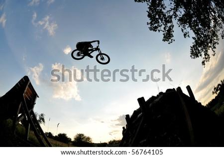 Silhouette of a man doing a mountain bike jump - stock photo