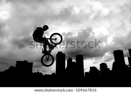 Silhouette of a man doing an extreme jump with a mountain bike .