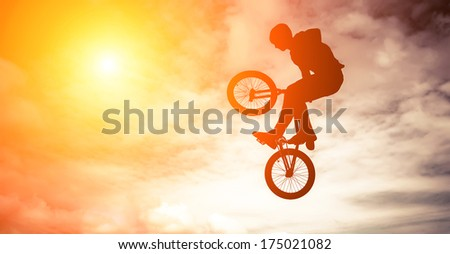 Silhouette of a man doing an jump with a bmx bike against sunshine sky. - stock photo