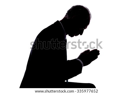 Silhouette of a man expressing prayer - stock photo