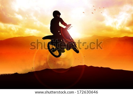 Silhouette of a man figure riding a motocross - stock photo