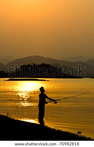 Silhouette of a man fishing in a sunset, Thailand - stock photo