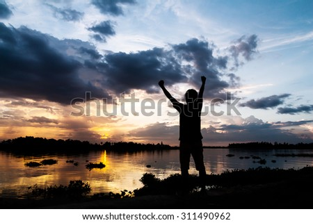 Silhouette of a man hold his hands as indicating success beside the river at sunset - stock photo