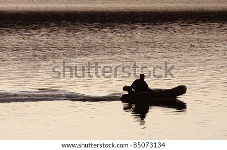 silhouette of a man in a boat on the water, the trace of the boat