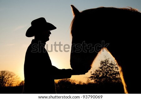 Silhouette of a man in a cowboy hat with his horse against sunset - stock photo