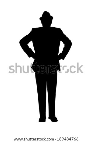 Silhouette of a man in a suit and hat with his hands on his hips as though observing something isolated on white. - stock photo