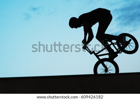 silhouette of a man on a bmx
