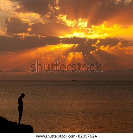 Silhouette of a man on a cliff above the sea at sunset - stock photo