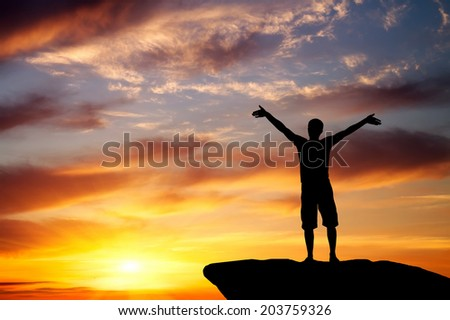 Silhouette of a man on a mountain top on fiery orange background  - stock photo