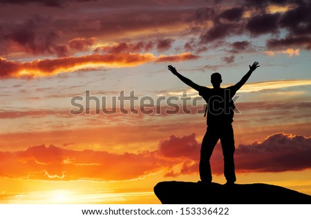Silhouette of a man on a mountain top on sunset sky background - stock photo