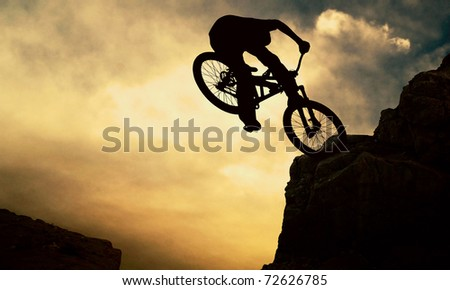Silhouette of a man on muontain-bike, sunset - stock photo