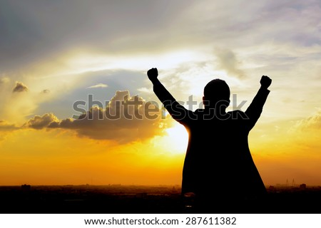 Silhouette of a man raising his arms in twilight sky background - success, winning & accomplished concepts