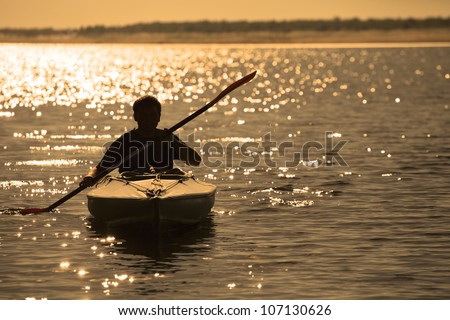 Silhouette of a man rowing in the canoe - stock photo