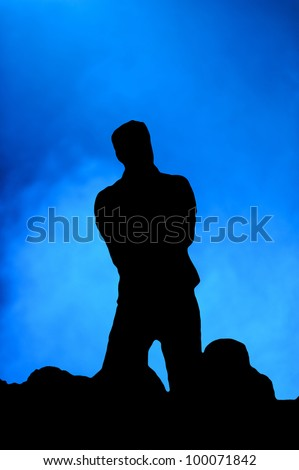 Silhouette of a man singing on stage in front of an audience against a blue background