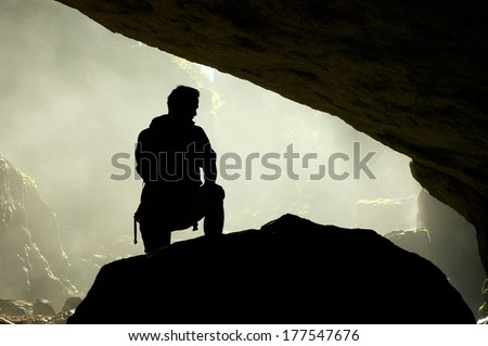 Silhouette of a man standing in front of a cave entrance  - stock photo
