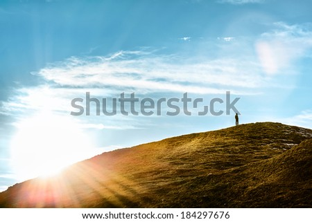 Silhouette of a man standing on a hill thinking in sunlight - stock photo