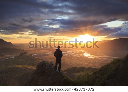 Silhouette of a man standing on a ridge, enjoying the sunset over a river valley in Thorsmork, Iceland.