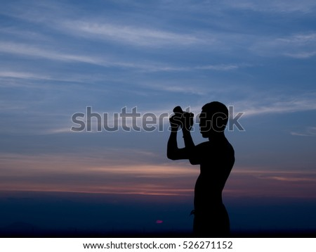 Silhouette of a man taking a picture in twilight time