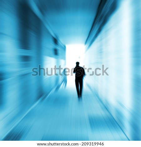 Silhouette of a man walking in a tunnel. - stock photo