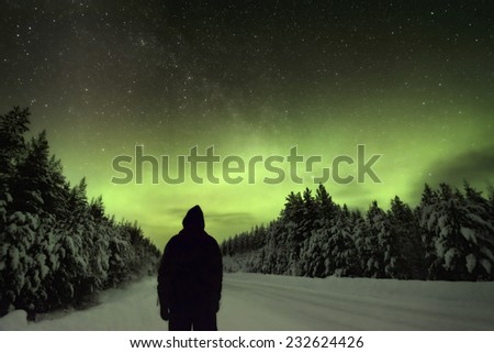 Silhouette of a man watching the Northern Lights Aurora Borealis - stock photo